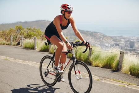 Vrouw oefenen voor triathlon concurrentie. Triathlon atleet fietser down hill op landweg. Jonge vrouw rijdt fiets op openbare weg. Stockfoto