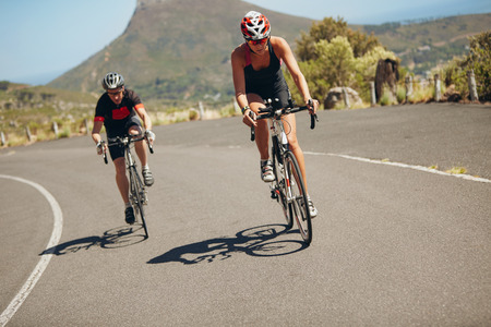 Cyclist riding bikes on open road. Triathletes cycling down the hill on bicycles. Practicing for triathlon race on country road. Stock Photo