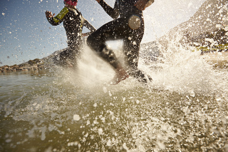 Dos participantes del triatlón que se ejecutan en el agua para natación parte de la raza. Bienvenida de agua y los atletas corriendo. Centrarse en las salpicaduras de agua.
