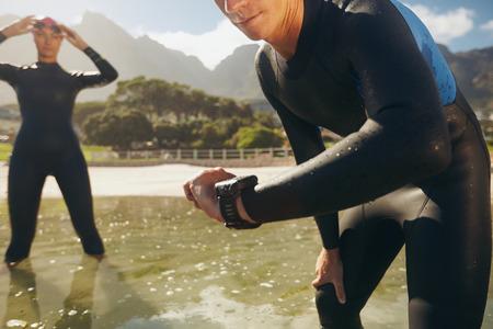 Man checking his timer. Athletes in wet suits preparing for triathlon competition.