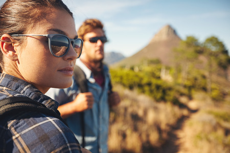 Close up image of young woman wearing sunglasses looking away with young man in background. Caucasian couple hiking in countryside.