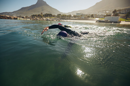 swimming race: Athletes in the swim event of a triathlon competition. Triathletes swimming in open water. Stock Photo