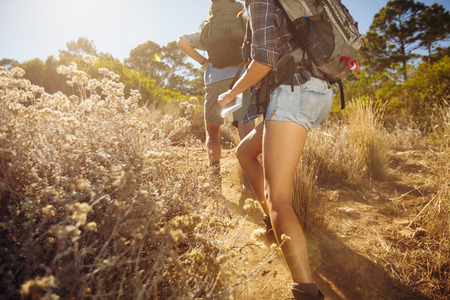 hiking path: Cropped image of man and woman walking on country trail path. Young couple hiking on mountain on sunny day.