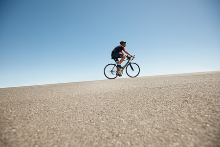 road cycling: Low angle image of a male cyclist riding on a flat road against blue sky. Man cycling up hill on open road.