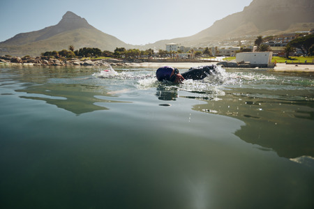 sportsperson: Male athlete swimming in open water. Athlete practicing for the triathlon competition.