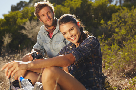 outdoors woman: Portrait of happy young woman with her boyfriend taking a break on a hike. Couple hiking on summer vacation, Woman looking at camera smiling with man sitting behind.