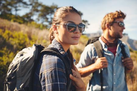 gafas de sol: Mujer bonita joven en un viaje de senderismo con el hombre en el fondo. Pares caucásicos en alza en el campo Foto de archivo
