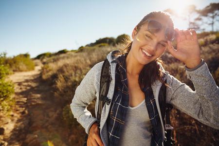 libertad: Retrato de una mujer joven feliz excursionista en la naturaleza. Caucásica mujer con gafas de sol joven que mira a la cámara con una mochila en un día de verano. Ecoturismo y concepto de la libertad Foto de archivo