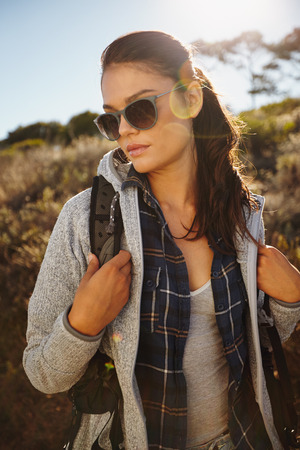 people travelling: Portrait of an attractive young female hiker in nature. Caucasian young woman wearing sunglasses and carrying a backpack looking away with sun flare. Stock Photo
