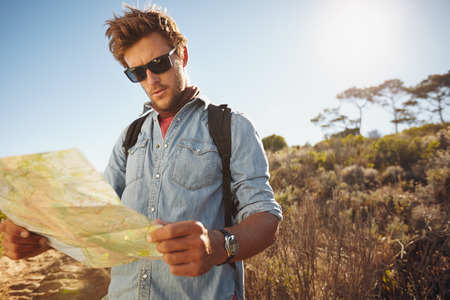 one young man: Shot of a handsome hiker using a map. Hiker using a map to navigate his hike on a summer day.