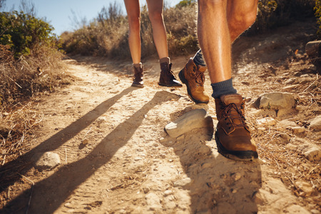 Close-up of legs of young hikers walking on the country path. Young couple trail waking. Focus on hiking shoes.