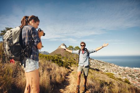 하이킹하는 동안 시골에서 그녀의 남자 친구를 촬영하는 젊은 여자의 야외 촬영. 여름 방학 동안 즐기는 등산객 몇입니다. 스톡 콘텐츠
