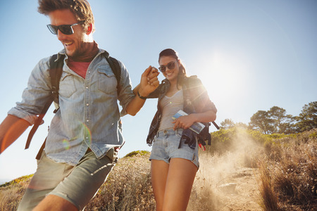 Outdoor shot of happy young couple enjoying on their hiking trip, walking down the mountain trail smiling. Caucasian couple having fun on summer vacation.