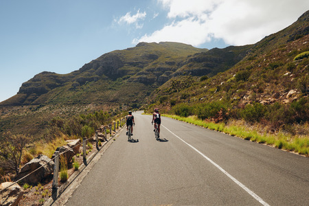 road cycling: Rear view of two cyclist riding down the country road through mountains. Cycling event of triathlon competition. Triathletes practicing cycling on open country road.
