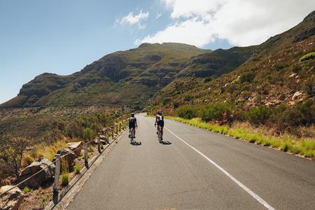ciclismo: Vista trasera de dos ciclista en la carretera pa�s a trav�s de las monta�as. Evento de Ciclismo de la competencia del triatl�n. Los triatletas practicando ciclismo en carretera abierta pa�s. Foto de archivo