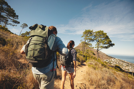 backpack: Rear view of two young people walking down the trail path on mountain. Young couple hiking with backpacks. Stock Photo