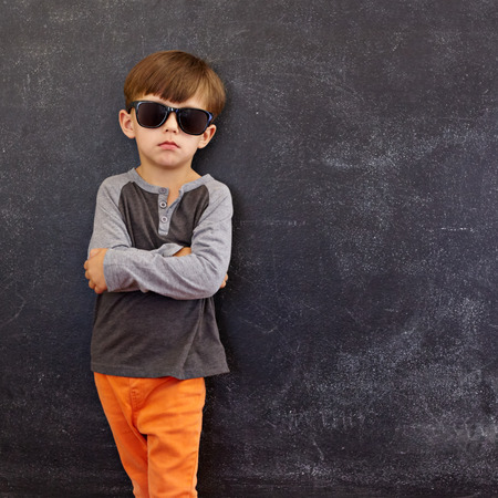 Portrait of smart little boy wearing sunglasses standing with his hands folded against blackboard with copyspace.