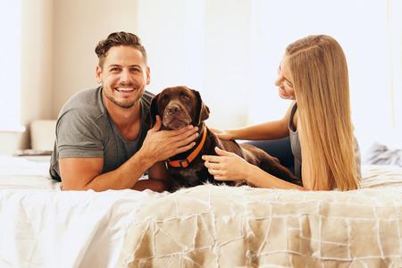 mimos: Retrato de la joven pareja feliz en la cama con el perro en la mañana. Hombre acariciar al perro y sonriendo.