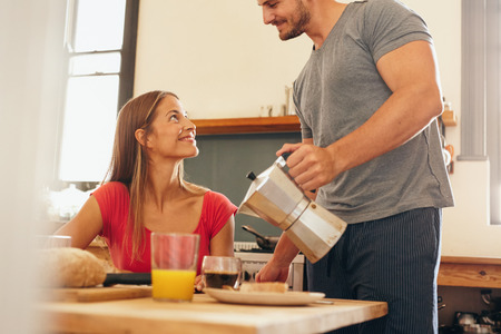 servings: Shot of young couple having breakfast in kitchen. Young man standing and serving coffee with woman sitting by breakfast table at home in domestic kitchen.