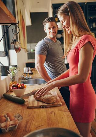 朝のキッチンで白人カップルが一緒。若い女性の切削パン、そばに立っている彼女の夫に焦点を当てます。朝食用食品を準備します。 写真素材