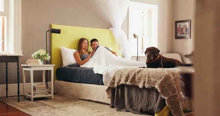Indoor shot of young couple sharing a digital tablet while relaxing in bed at home. Couple on bed and using a digital tablet together with pet dog. Stock Photo