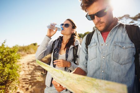 man drinking water: Couple on country walk together, summer vacation in countryside. Young man reading a map while woman drinking water in background.