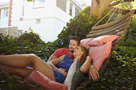 couple relaxing: Young couple relaxing on a garden hammock. They are looking away in thought. Relaxed man and woman swinging on a hammock in backyard.