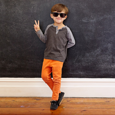 fashion boy: Full length shot of cool little boy wearing sunglasses gesturing victory sign. Young school boy in casuals showing peace symbol while leaning on a black wall at home.
