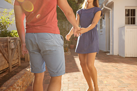 hands holding house: Cropped shot of young couple standing in front of their house holding hands. Man and woman in casuals outside their home on a summer day.