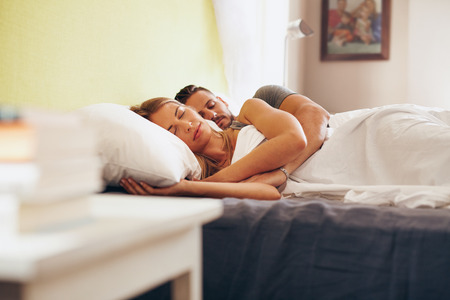 Young adult couple sleeping peacefully on the bed in bedroom. Young man embracing woman while lying asleep in bed. Banque d'images