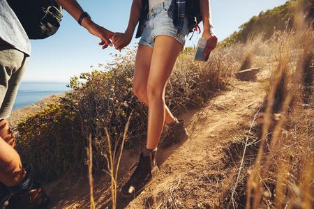 근접 하이킹 여행 젊은 부부의 샷. 산길을 걷는 동안 손을 잡고 젊은 남자와 여자 등산객의 자른 이미지입니다.