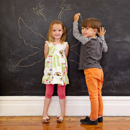 blackboard: Full length portrait of cute little girl standing and little boy drawing angel wings around her on blackboard. Two little kids standing in front of blackboard at home looking at camera smiling.