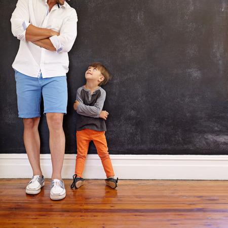 Plan intérieur d'un petit garçon et de son père debout, les mains jointes contre un mur noir. Père et fils se regardant avec espace de copie. Fils imitant la pose de son père.
