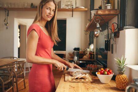 Mooie jonge vrouw snijdt een vers gebakken brood van brood in een binnenlandse keuken. Blanke vrouw kijkt naar de camera, terwijl de voorbereiding ontbijt.