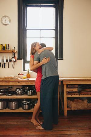 parejas felices: Mujer joven feliz de ser abrazada por su novio en la cocina. Alegre joven pareja abrazándose en la mañana en su casa. Foto de archivo
