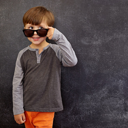 child portrait: Portrait of a little boy in sunglasses looking at away at copy space. Cool boy peering over his sunglasses against blackboard. Stock Photo