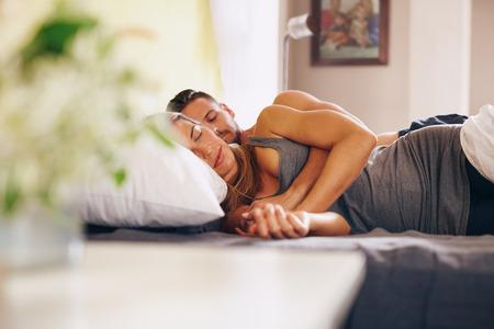 couple bed: Image de jeune couple dormir � poings ferm�s dans le lit ensemble. Mari et femme dormir ensemble dans leur chambre � coucher.