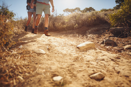 Low angle view of two people hiking along a dirt trail in the wilderness.  Couple of hikers walking on country path. 写真素材