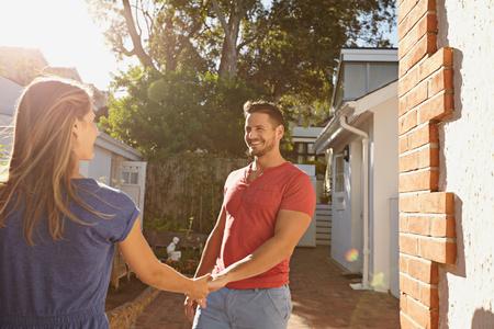 dia soleado: Hombre joven feliz de la mano de su novia y caminar alrededor de su casa. Amante de la joven pareja al aire libre en su patio trasero en un día soleado brillante.