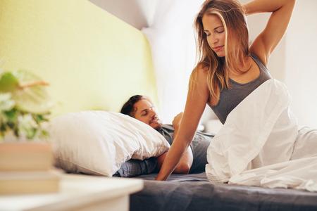 esposas: Retrato de la hermosa mujer joven que despierta por la ma�ana con su marido durmiendo tranquilamente detr�s de ella Foto de archivo