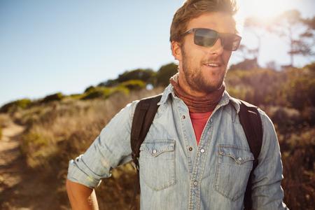 Portrait eines glücklichen jungen Mann Wandern in der Landschaft. Caucasian Dressman mit Rucksack Wandern an einem sonnigen Tag. Sommerferien in der Landschaft.