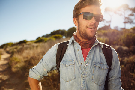 Portrait of happy young man hiking in countryside. Caucasian male model with backpack hiking on sunny day. Summer vacation in countryside. Stock Photo