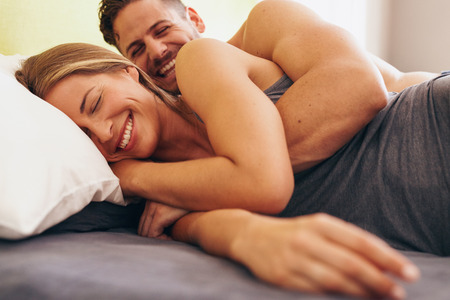 Image of cute young couple in love lying on bed. Man waking up his wife in morning. Stock Photo