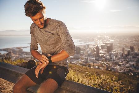 Hombre joven que ajusta su reloj GPS antes de una carrera. Montar deportista joven sentado en la barandilla carretera y mirando el reloj mientras que salir a correr por la mañana.