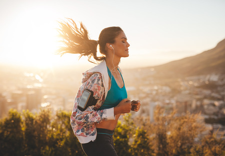 Portrait of beautiful young woman out for a run on a hot sunny day. Caucasian female model jogging outdoors. Standard-Bild