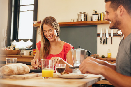 eating: Happy young couple having breakfast together at home. Young woman and man smiling while eating breakfast in kitchen. Couple having good time during breakfast in kitchen. Stock Photo