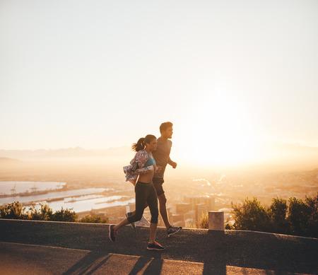 hacer footing: Foto de la joven pareja corriendo juntos en el camino de la ladera. Hombre joven y una mujer corriendo juntos en la mañana temprano. Foto de archivo