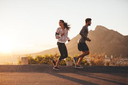 Pareja joven trotar temprano en la mañana, con la mujer mirando hacia atrás por encima del hombro. Hombre joven y mujer corriendo al aire libre en un camino rural.