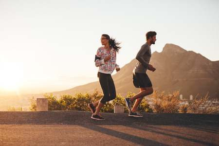 espalda: Pareja joven trotar temprano en la mañana, con la mujer mirando hacia atrás sobre su hombro. Hombre joven y una mujer corriendo al aire libre en un camino rural.