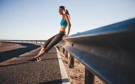 guardrail: Outdoor shot of happy young woman sitting on highway guardrail after a morning run. Fit woman on country road taking a break after outdoor workout. Stock Photo
